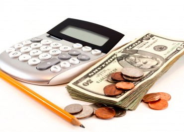 Personal finance and accounting with calculator, money and yellow pencil isolated on white background.. Image shot 2012. Exact date unknown.